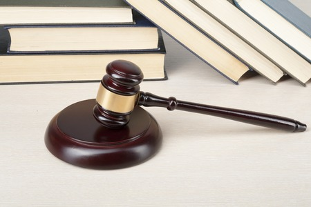 Law concept - Book with wooden judges gavel on table in a courtroom or enforcement office. Stock Photo
