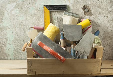 Wooden box with construction tools for repair on background old wall. 写真素材