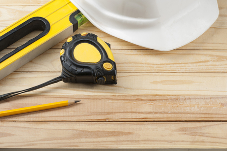 Construction tools and white helmet on wooden background .Copy space for text. Banque d'images