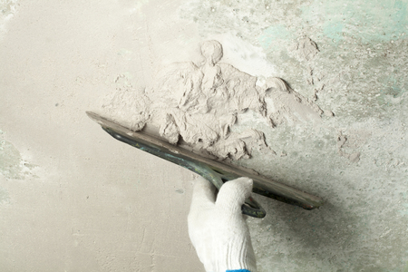 Construction and renovation concept. Hand of man in glove with trowel during repair of wall. Stock Photo