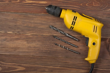 Yellow electric drill on a wooden background.Copy space for text. Construction concept.