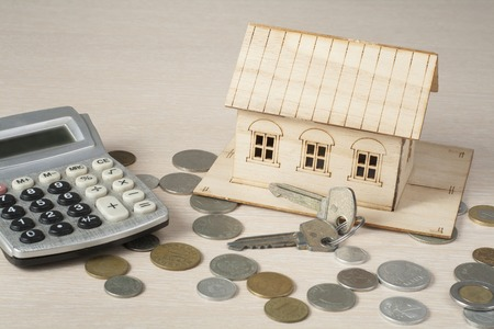Home savings, budget concept. Model house, calculator, keys and coins on a beige background. Banque d'images