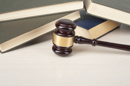 Law concept - Book with wooden judges gavel on table in a courtroom or enforcement office. 免版税图像