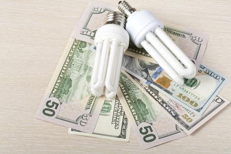 Energy saving fluorescent lamp on money background, Eco light bulb, comparison of energy saving lamps and incandescent lamps.Energy saving and saving electricity concept Imagens