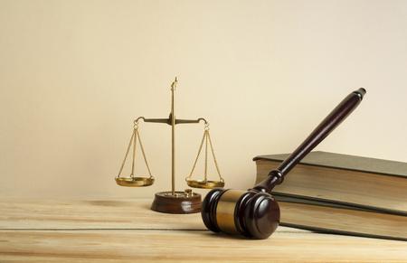 Wetsconcept. Houten rechter hamer, schalen van Justitie en boeken op tafel in een rechtszaal of handhavingskantoor.