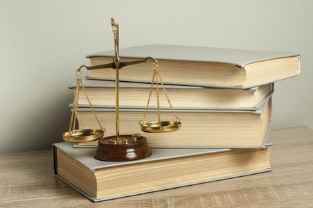 Gesetz Konzept. Waage der Gerechtigkeit mit Gesetzesbüchern auf dem Tisch in einem Gerichtssaal oder einem Vollstreckungsbüro.