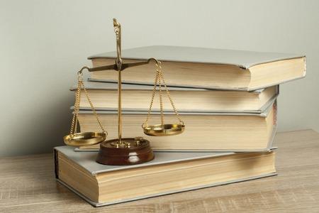 Wetsconcept. Schalen van Justitie met wetboeken op tafel in een rechtszaal of handhavingskantoor.