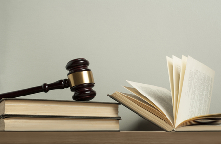 Law concept. Wooden judge gavel with law books on table in a courtroom or enforcement office.