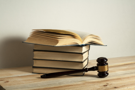 Law concept. Wooden judge gavel with law books on the table in a courtroom or enforcement office.