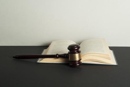 Notion de droit. Marteau de juge en bois et livre ouvert sur table dans une salle d'audience ou un bureau d'exécution. Banque d'images