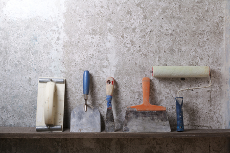Construction tools on concrete background. Copy space for text. Set of assorted plaster trowel and spatula Imagens
