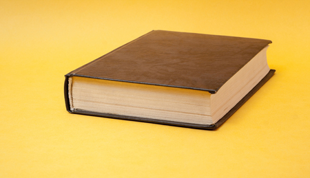 Old book on yellow background. Back to school. Education concept. Imagens