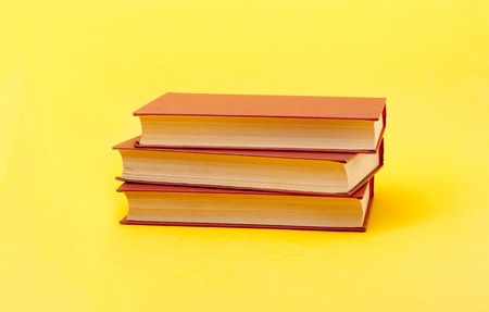 Red books on yellow background. Education concept. Back to school.