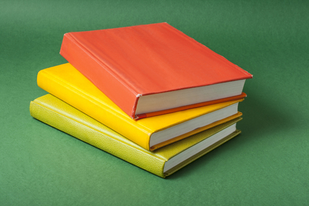 Colorful books on green background. Back to school. Education concept.