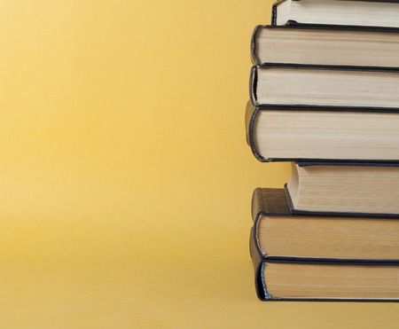 Stack of books on yellow background. Education concept. Back to school. Imagens