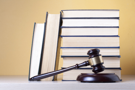 Law concept - Book with wooden judges gavel on table in a courtroom or enforcement office. Imagens