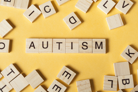 Text AUTISM on wood cubes. Wooden abc