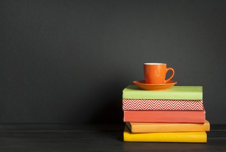 Stack of colorful books and cup of coffee on the wooden table. Education background. Back to school.Copy space for text.