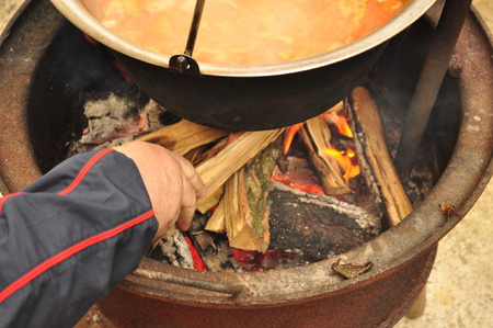 under fire: Firewood refill the fire under the goulash soup
