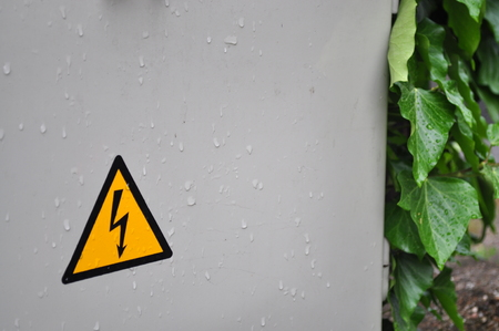 high voltage sign: Yellow high voltage sign with rain leaf contrast photo