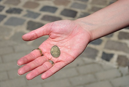 her: One golden colour Souvenir coin in her hand Stock Photo