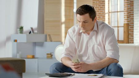 Boos zakenman in problemen met het tellen van geld, schuld op hypothecaire lening, faillissement