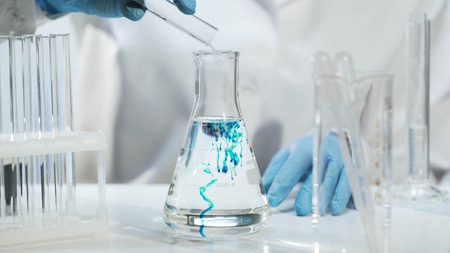 Chemist pouring substance into conical flask with liquid, chemical experiment