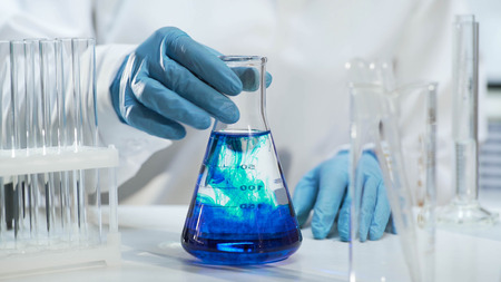 View of conical flask with liquid changing color into blue, biochemistry