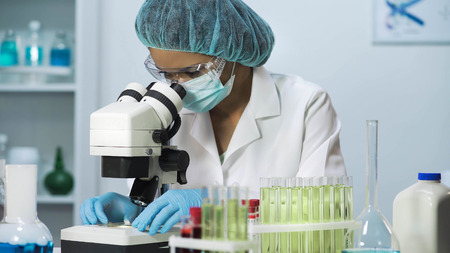 Woman scientist looking into microscope, biochemical research, cosmetology Stock Photo