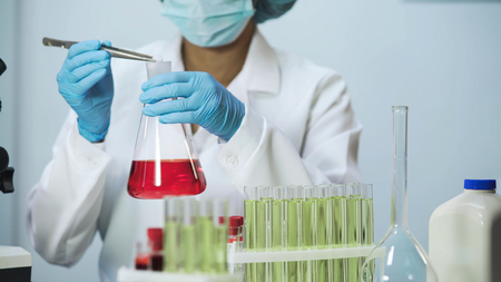 Female lab assistant putting reagent into the flask, doing cosmetology research Stock Photo