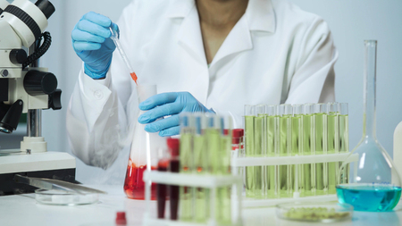 Female biochemist working at laboratory, taking sample of liquid from the flask