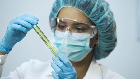 Attractive lab assistant analyzing biomaterial in tubes, biochemical research Stock Photo