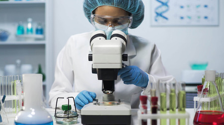 Female laboratory technician looking into microscope, doing biomedical research