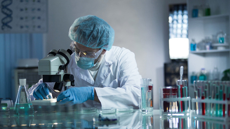Medical lab worker examining laboratory glass with sample through microscope