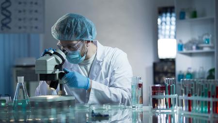Laboratoriumarbeider onderzoekt zorgvuldig monsters om chronische pathologieën te detecteren Stockfoto