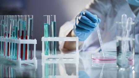 Stagiaire chimiste mélangeant des liquides, en attente d'une réaction chimique au laboratoire scientifique