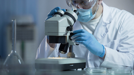 Biologist carefully examining cell particles, carrying course of investigations Stock Photo