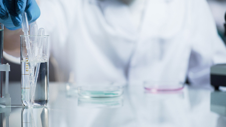 Laboratory worker checking viscosity and kinetic abilities of substance, science