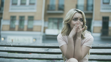 Sad young lady sitting alone and crying bitterly, relationship or health problem