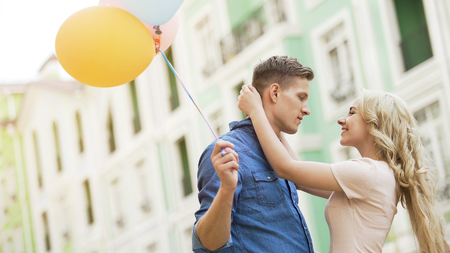Blonde girl embracing beloved young man couple dating holding balloons