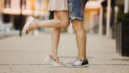 Legs of flirty girlfriend and boyfriend in love hugging and kissing in street