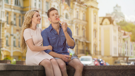 Guy in love making soap bubbles, girlfriend in love sitting next to him, date