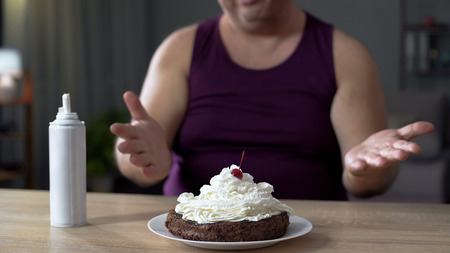 Corpulent man looking at chocolate cake with whipped cream, unhealthy food