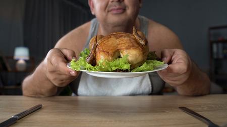 太りすぎの油鶏のグリル楽しさ、不健康な食べ物の臭いがする男