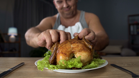 Bad-mannered overweight man tearing piece of chicken with hands, overeating Stock Photo