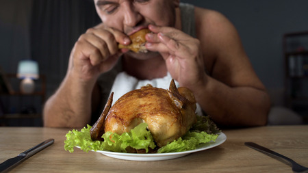 Plump male eating fatty fried chicken hungrily, high-calorie food and addiction