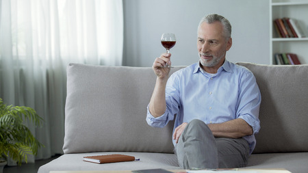 Pleased man in his 50s sitting on couch and tasting red wine sniffing aroma