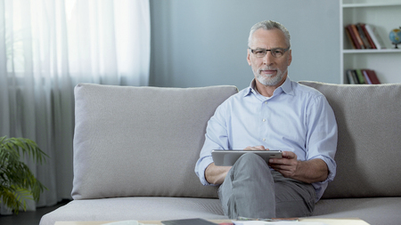Good-looking adult man sitting on sofa and scrolling on tablet application