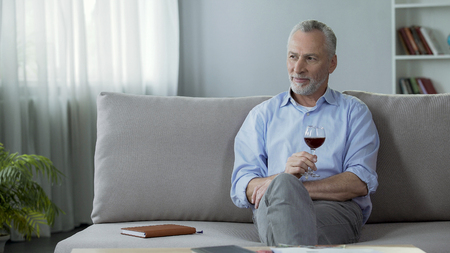 Happy adult person sitting on sofa drinking red wine and thinking about life Stock Photo