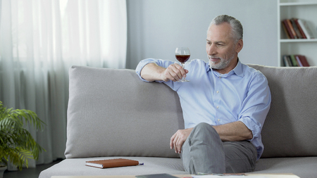 Handsome senior man sitting on couch and enjoying perfect wine taste and aroma Stock Photo
